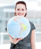 Assertive businesswoman holding a globe Royalty Free Stock Photos
