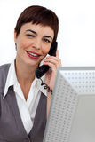 Assertive Businesswoman on phone at her desk Royalty Free Stock Photo