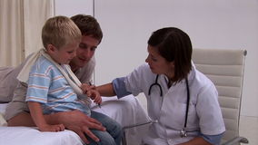 Assertive doctor examining a little boys arm Royalty Free Stock Image