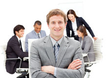 Assertive male executive with folded arms. Sitting in front of his team in a meeting Stock Photo