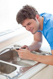 Assertive man repairing his sink in the kitchen Royalty Free Stock Images