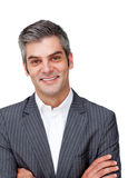 Assertive mature businessman with folded arms. Against a white background royalty free stock photography