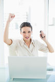 Assertive stylish brunette businesswoman raising her fist Stock Image