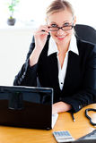 Assertive woman with glasses working on laptop Stock Photo