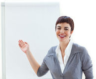 Assertive young businesswoman pointing at a board Stock Photo