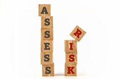 Assess Risk word written on cube shape. Assess Risk word written on cube shape wooden surface isolated on white background Royalty Free Stock Photography