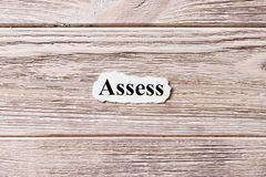 ASSESS of the word on paper. concept. Words of ASSESS on a wooden background.  royalty free stock photo