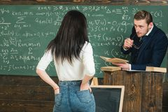 Assessing student learning outcomes. Teacher listen to girl student in classroom. Rear view woman in jeans answer to man. Assessing student learning outcomes royalty free stock photos