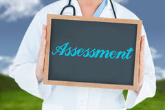 Assessment against field and sky. The word assessment and doctor showing chalkboard against field and sky stock photos