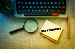 ASSESSMENT wording on notebook with typewriter ,pen and magnifying glass on wooden table. Stock Images