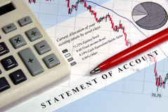 Asset Statement With Down Graph. Asset statement, declining graph line, calculator, and pen Royalty Free Stock Photography