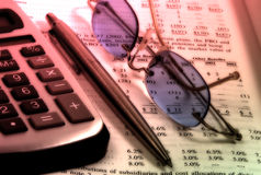 Assets. Photo of a Calculator, Pen, Glasses and Balance Sheet With Color and Blur Effect Royalty Free Stock Photos