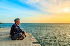Asseyez-vous et en regardant au coucher du soleil Photo stock