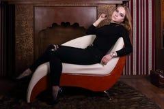 Assez blond dans des poses noires sur le tabouret Photo stock
