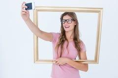 Assez blond prenant un selfie d'elle-même tenant le cadre images libres de droits