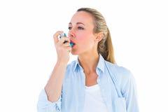 Assez blond utilisant un inhalateur d'asthme images libres de droits