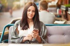 Assez femelle avec l'expression, les prises téléphone intelligent et les types réfléchis message textuel, enveloppé dans la couve Photo libre de droits