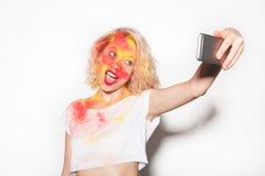 Assez femelle dans des couleurs de Holi prenant le selfie Photo stock