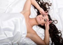 Assez femelle dans le peignoir dormant sur le lit sous les feuilles en soie Images libres de droits
