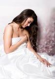 Assez femelle dans le peignoir dormant sur le lit sous les feuilles en soie Image libre de droits