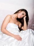 Assez femelle dans le peignoir dormant sur le lit sous les feuilles en soie Images stock