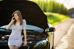 Assez, jeune femme appelle le service/aide de bord de la route Photo stock