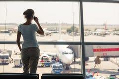 Assez, jeune femme attendant à un secteur de porte d'un aéroport moderne Photo stock