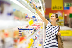 Assez, jeune femme avec les épiceries de achat d'un panier à provisions Image stock