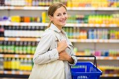 Assez, jeune femme avec les épiceries de achat d'un panier à provisions Photographie stock libre de droits