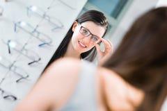 Assez, jeune femme choisissant de nouveaux cadres en verre Image libre de droits