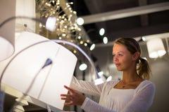 Assez, jeune femme choisissant la bonne lumière pour son appartement i Images stock