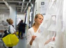 Assez, jeune femme choisissant les rideaux droits pour ses apartmen Photo libre de droits