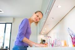 Assez, jeune femme nettoyant sa cuisine moderne Photos libres de droits
