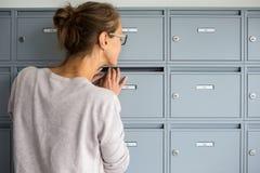 Assez, jeune femme vérifiant sa boîte aux lettres Images libres de droits