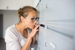 Assez, jeune femme vérifiant sa boîte aux lettres image libre de droits