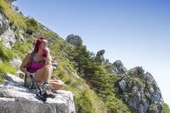 Assez le milieu a vieilli le randonneur féminin se reposant sur la grande roche Photos libres de droits