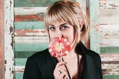 Assez un blond dans la robe noire tenant un bâton de sucrerie rouge à h images stock