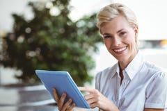 Assez un blond heureux utilisant la tablette image stock