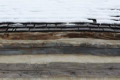 Assicelle di legno innevate su un granaio del ceppo fotografia stock libera da diritti