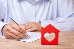 Assicurazione, affitto o acquisto domestico di concetto La casa rossa con cuore e l'uomo firma il contratto immagine stock libera da diritti