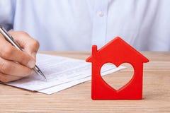 Assicurazione, affitto o acquisto domestico di concetto La casa rossa con cuore e l'uomo firma il contratto Fotografia Stock Libera da Diritti