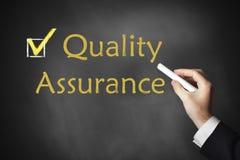 Assicurazione di qualità di scrittura della mano sulla lavagna immagine stock