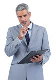 Assiduous businessman holding clipboard and taking notes Stock Photo