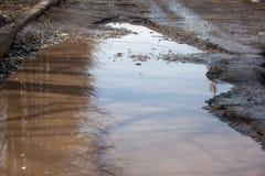 Assiette de la route détruite dangereuse La route asphaltée par mauvais Grand nid de poule rempli avec de l'eau image stock