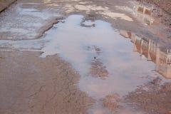 Assiette de la route détruite dangereuse La route asphaltée par mauvais Grand nid de poule rempli avec de l'eau photos stock
