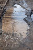 Assiette de la route détruite dangereuse Le mauvais a asphalté la route avec un grand nid de poule rempli avec de l'eau photos libres de droits