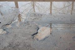 Assiette de la route détruite dangereuse Le mauvais a asphalté la route avec un grand nid de poule rempli avec de l'eau photographie stock libre de droits
