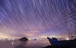 For assignment files Startrails over the boat. The stars full of the sky over the east bay of China were shining brightly.There was a boat by the beach of the stock photo