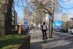 Assinante fêmea da bicicleta em Londres, Inglaterra, energia verde, cena urbana, transporte Imagem de Stock