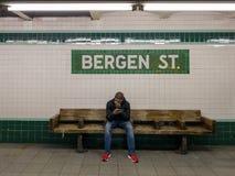 Assinantes que esperam em Bergen Street Subway Station em Brooklyn, New York ao longo da linha de F fotografia de stock